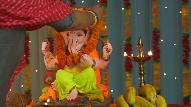 Overhead shot of an Indian female garlanding Lord Ganesha idol and praying on Ganesh Chaturthi