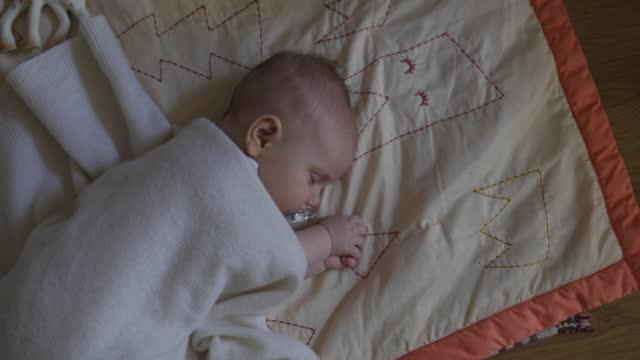 Overhead Shot of Baby Sleeping on Floor Covered with Blanket