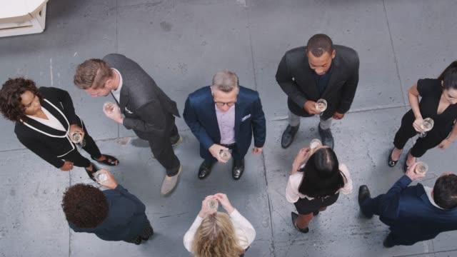 vídeos y material grabado en eventos de stock de toma aérea de equipo de negocios socializando con bebidas en la reunión después del trabajo en la oficina moderna - zoom meeting