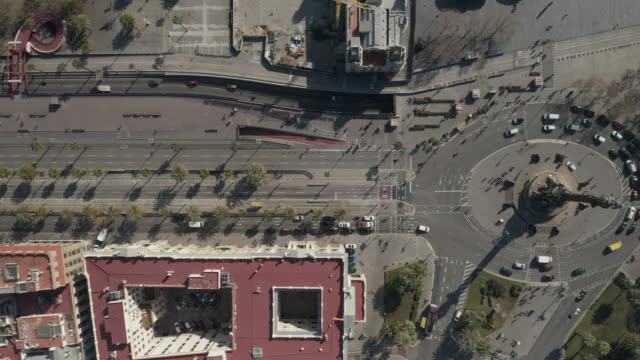 aerial: overhead shot of columbus monument roundabout and street in barcelona, spain with busy car traffic on sunny day [4k] - balaustrata video stock e b–roll
