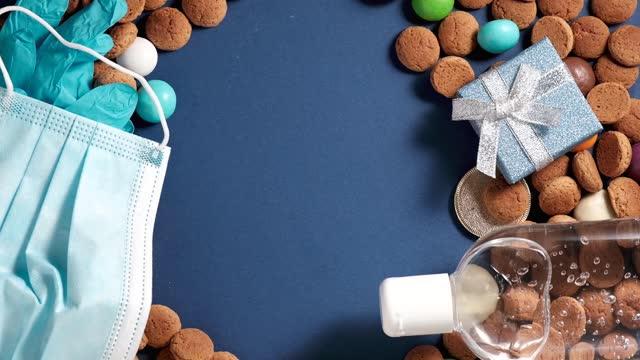 stockvideo's en b-roll-footage met overhead shot van nederlandse vakantie sinterklaas sinterklaas sinterklaasdag tijdens covid-19 pandemie in nederland met kruidnoten koekjes, traditionele snoepjes, medische beschermingsmiddelen. roterende, kopieerruimte - pepernoten