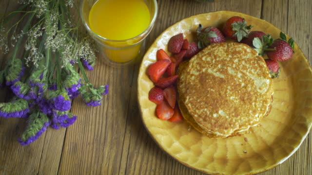 inquadratura dall'alto di prima colazione gourmet di fragole, succo d'arancia e pancake - buffet video stock e b–roll