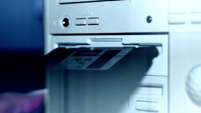 vídeos y material grabado en eventos de stock de toma de sobrecarga de alguien que inserte y quite un disquete de 3,5 pulgadas de estilo antiguo. profundidad de campo poco profunda. - disquete