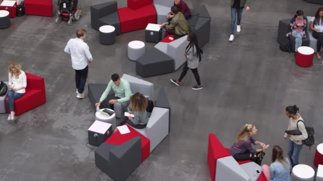 vídeos de stock, filmes e b-roll de tiro aéreo de estudantes em um lobby de universidade ocupado, filmado em r3d - college people laptop