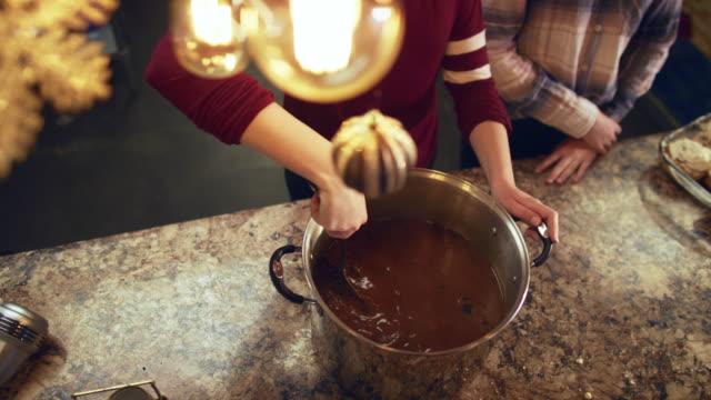 兩個女孩在廚房的櫃檯頂部被打得頭蓋不甯一大罐熱巧克力 - 焗 預備食物 個影片檔及 b 捲影像