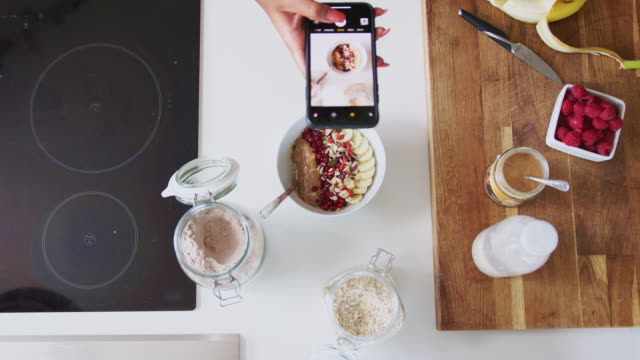 overhead shot of woman taking picture of healthy breakfast on mobile phone at home after exercise - kompozycja flat lay filmów i materiałów b-roll