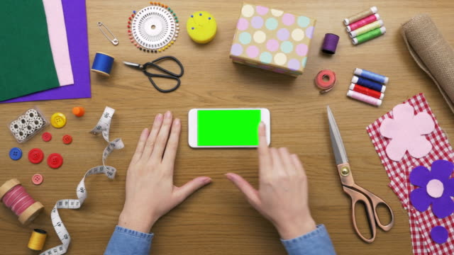 Overhead Shot Of Woman Using Smartphone Surrounding Sewing Tools