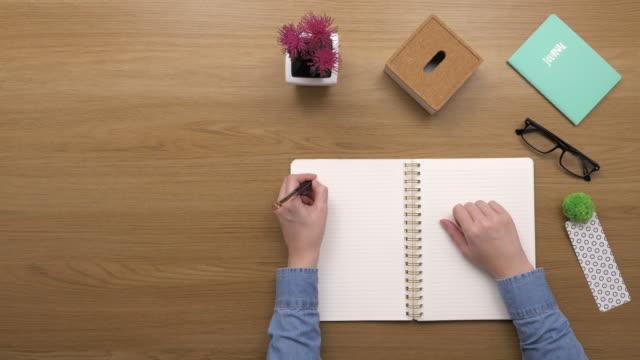 vidéos et rushes de frais généraux top view of femme faire des to-do liste dans diary - agenda