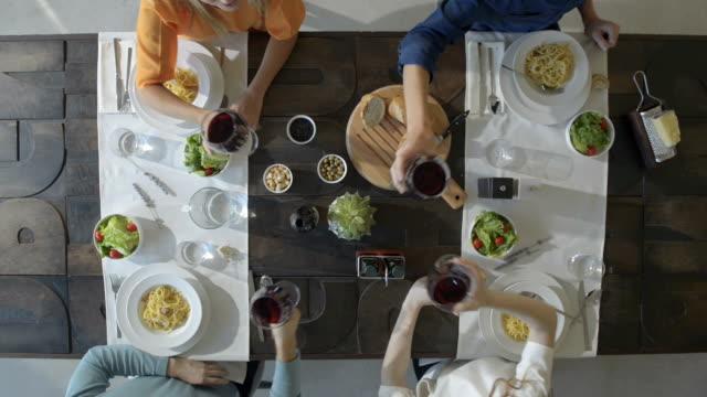 stockvideo's en b-roll-footage met overhead bovenaanzicht tabel vier kaukasische vrienden carbonara italiaanse spaghetti pasta lunch of diner, eten drinken, roosteren samen met rode wijnglazen. de partij van de zomer thuis in moderne huis vide - restaurant table
