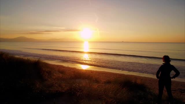 stockvideo's en b-roll-footage met overhead video van fit vrouw permanent op strand tijdens zonsondergang - handen op de heupen
