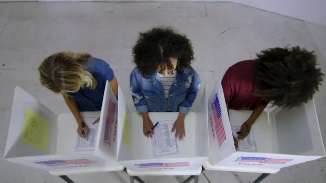 Overhead view Latina woman thinking while voting with other young women in slow motion video