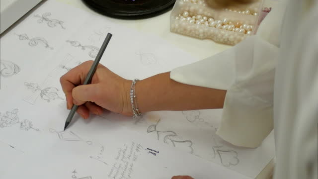 vídeos de stock e filmes b-roll de overhead view looking down jewelry designer in studio sketching out designs - jóias
