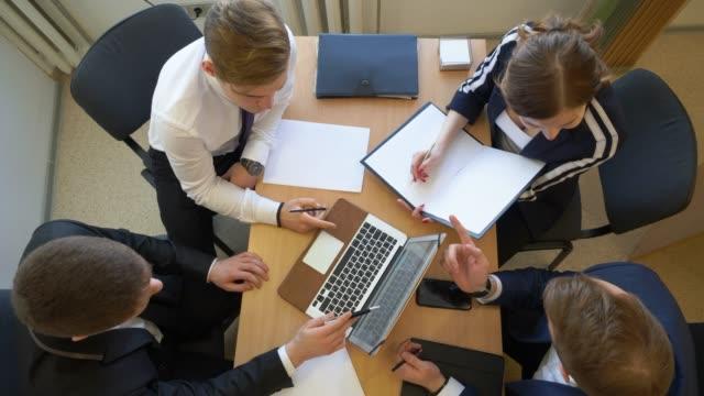 visualizzazione aerea degli uomini d'affari mani sulla scrivania di office utilizzando dispositivi elettronici - business meeting, table view from above video stock e b–roll