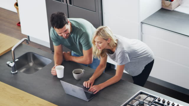 Overhead View Of Couple Looking At Laptop In Modern Kitchen video