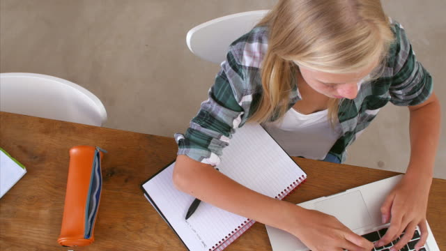 Overhead View Of Girl Doing Homework At Table On Laptop video