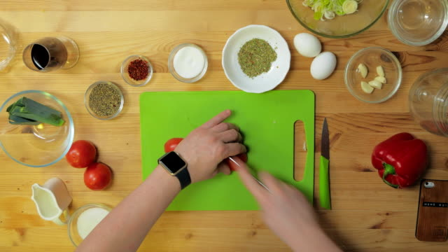 Overhead view of hand slicing a fresh garden tomato with large kitchen knife and whole tomatoes on cutting board video
