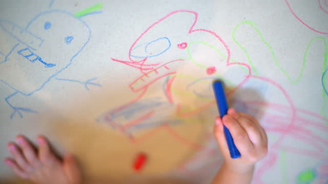 Overhead view of kindergarten kid drawing animal face on white paper.