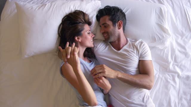 함께 침대에 누워 로맨틱 커플의 오버 헤드 보기 - 이성 커플 스톡 비디오 및 b-롤 화면