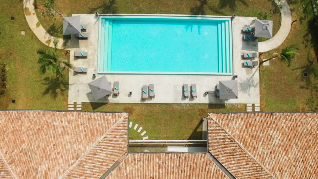 別荘の屋根とプールのオーバー ヘッド ビュー - 別荘点の映像素材/bロール