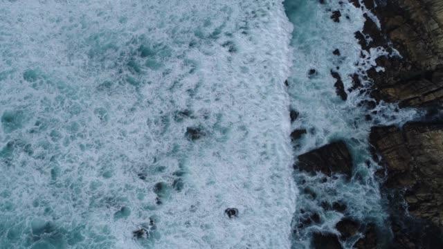 Overhead view of waves on rocks (4k)