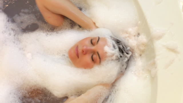 Overhead View Of Woman Washing Hair In Bubble Filled Bath video