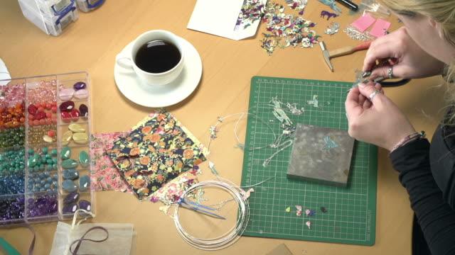 vidéos et rushes de vue aérienne de jeune femme fabriquer des bijoux à la maison - joaillerie