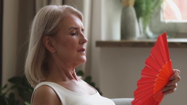 vídeos de stock, filmes e b-roll de ventilador quente idoso overheated da onda do sentimento da mulher em casa - ar condicionado