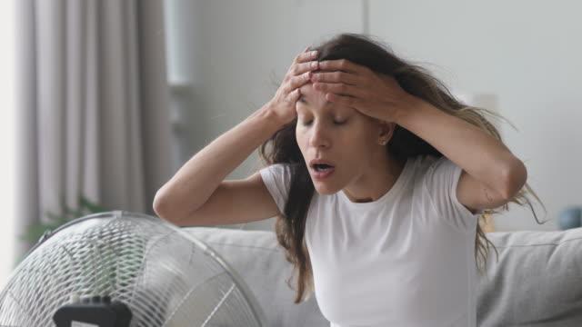 vidéos et rushes de la femme surchauffée souffrent de la chaleur s'asseyent devant le ventilateur - canicule