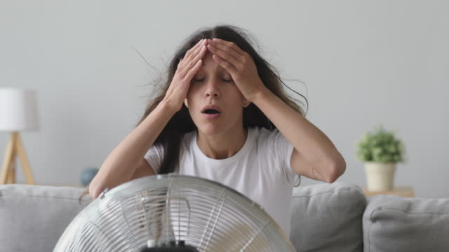 Overheated young mixed race girl sitting in front of ventilator. Overheated young mixed race girl sitting in front of ventilator, cooling herself alone without conditioner at home. Stressed unhappy millennial woman breathing fresh air from electric cooler. heat temperature stock videos & royalty-free footage
