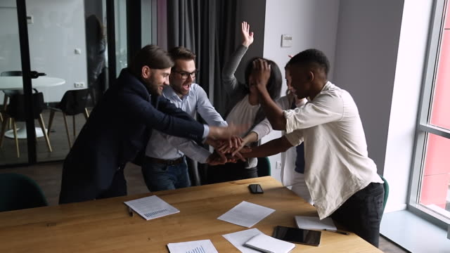 Overjoyed diverse business team stack hands together celebrate corporate success
