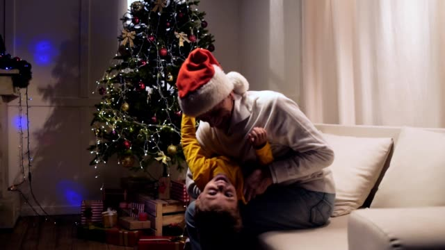 Overjoyed elderly man and his grandson having fun at home Constant jubilation. Cheerful delighted aged man having fun with his little smiling grandson sitting on the couch and resting together at home while waiting for Christmas setter dog stock videos & royalty-free footage