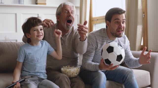 vídeos de stock, filmes e b-roll de muito feliz emocional três gerações masculinas família assistindo campeonato de futebol. - futebol