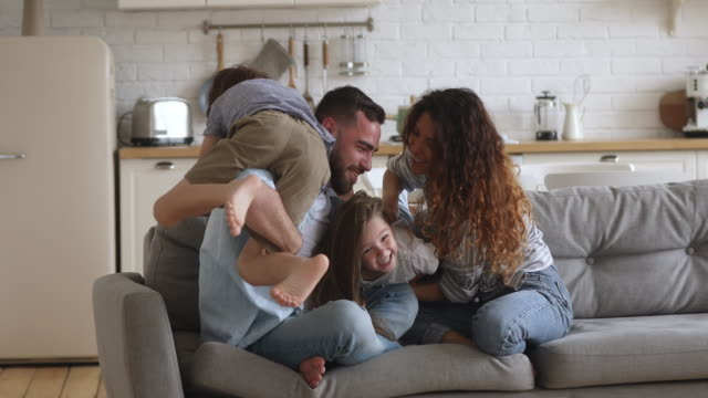 Overjoyed happy family of four enjoying leisure time at home.