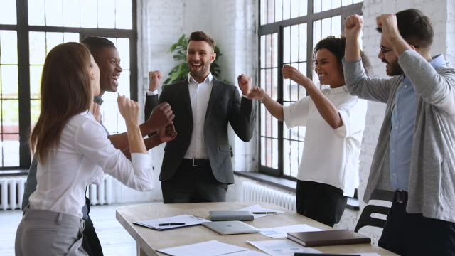 Overjoyed multiracial business team people celebrate triumph, slow motion