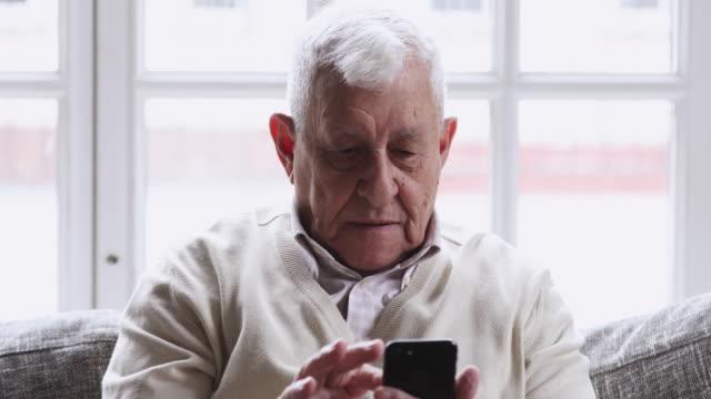 överlycklig senior man entusiastiska över mobilapp sport satsning vinna - lotteri bildbanksvideor och videomaterial från bakom kulisserna