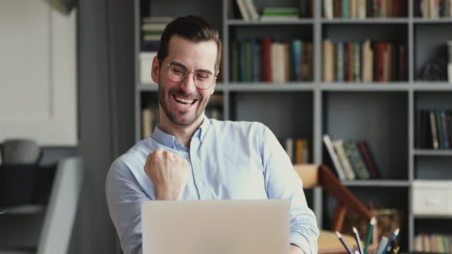 Overjoyed young businessman reading email on computer.