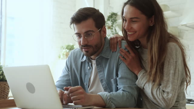 overjoyed young couple using laptop excited by online win - moglie video stock e b–roll