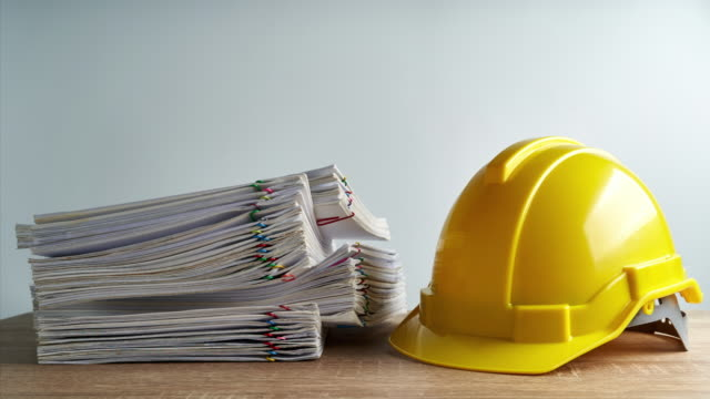 Overload report and engineer hat with copy space time lapse Pile of overload paperwork report of sale and receipt with yellow engineer hat on wood table and white background with copy space time lapse. Business and finance concepts successful footage. occupational safety and health stock videos & royalty-free footage