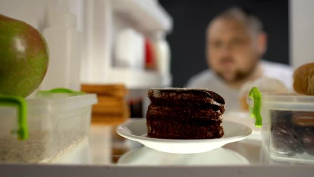 vídeos de stock e filmes b-roll de oversize man taking piece of cake from fridge at night, diabetes risk, calories - vício
