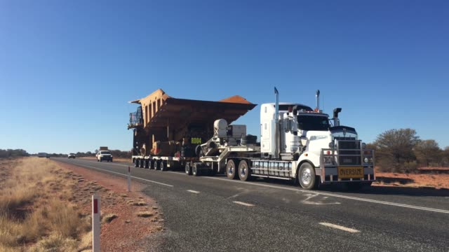 Oversize vehicle convoy on Stuart highway in the red center of Australia outback