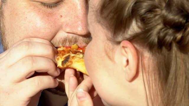 stockvideo's en b-roll-footage met oversized paar bijten calorierijke pizza slice, junkfood, overgewicht reden - dikke pizza close up