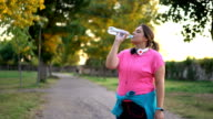 istock Oversized woman drinking water after running 1193028611