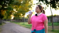 istock Oversized woman drinking water after running 1193029417