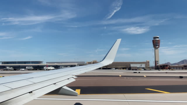 over-the-wing point of view des starts in einem kommerziellen-airliner-jet am phoenix sky harbor international airport in phoenix, arizona an einem sonnigen tag - amerikanische kontinente und regionen stock-videos und b-roll-filmmaterial