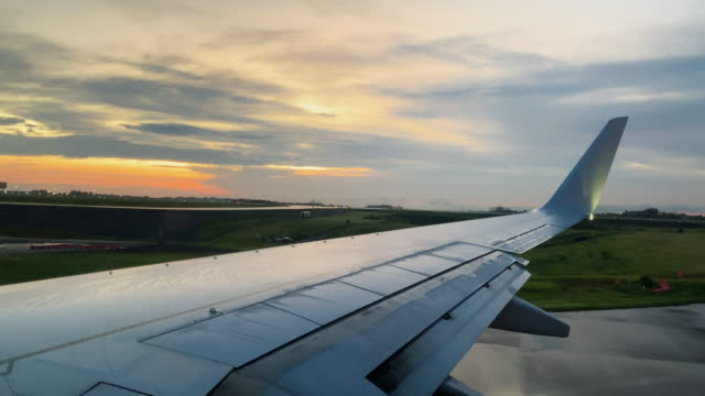 over-the-wing point of view of taxing down a runway in a commercial airliner jet at nashville international airport in tennessee at sunset - decollare attività video stock e b–roll