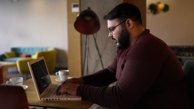 Overweight businessman using laptop in cafe