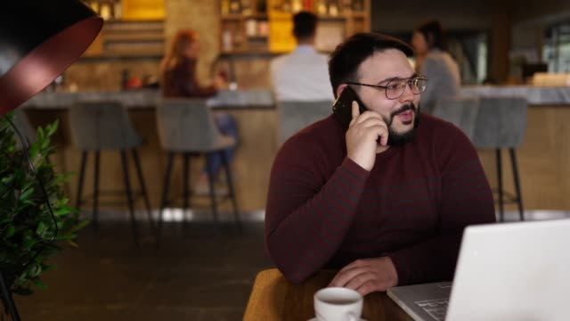 Overweight businessman using smart phone in cafe
