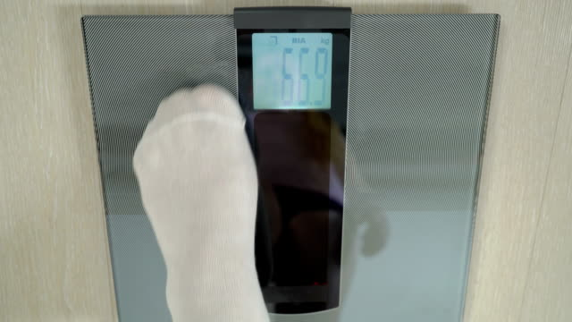 Overweight family one by one measuring body weight on digital bathroom scale video