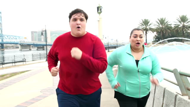 Overweight Hispanic couple jogging together video