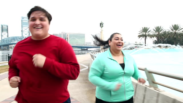 overweight hispanic couple jogging together - sovrappeso video stock e b–roll